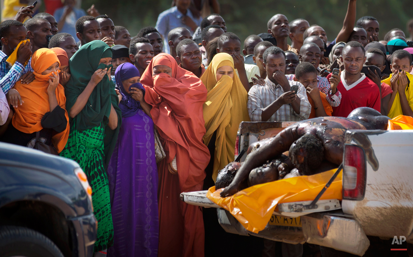 Women in the crowd cover their faces to protect against the smell as authorities display the bodies of the alleged attackers before about 2,000 people in a large open area in central Garissa, Kenya Saturday, April 4, 2015. (AP Photo/Ben Curtis)