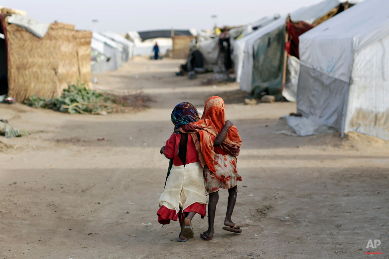 Ami and Ashbu, both three-years-old, walk  arm in arm  in the Zafaye refugee camp, some 15 kms (10 miles) from downtown N'djamena, Chad, Wednesday March 11, 2015. Both from the PK5 district of Bangui, have been living in the camp for over a year with  over 5000 other refugees of Chadian descent who fled the fighting in Central African Republic. Chad is also hosting thousands of refugees fleeing the current Boko Haram fighting in Nigeria. (AP Photo/Jerome Delay)