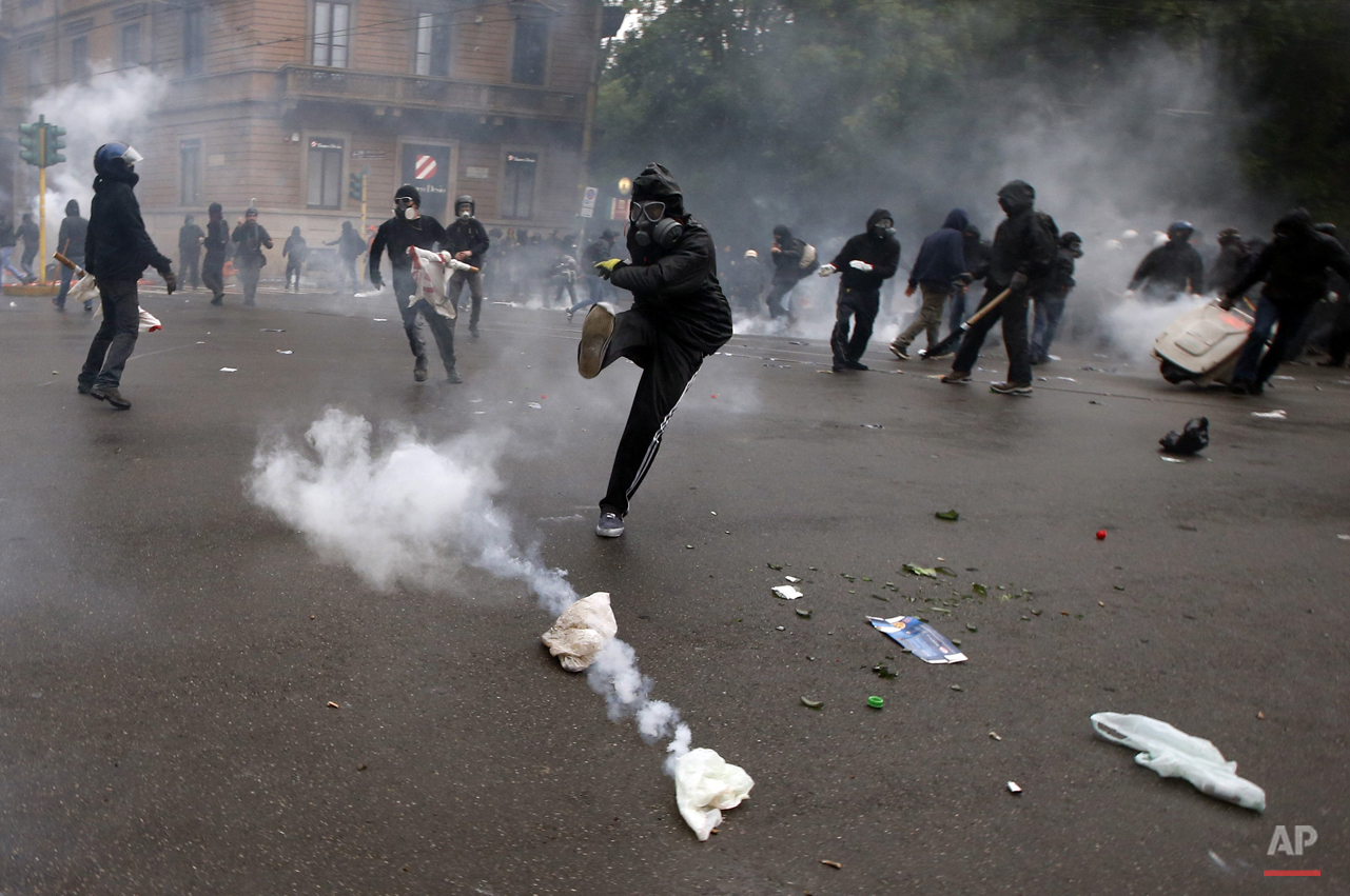 A demonstrators kicks a teargas canister as clashes broke out with  Italian Policemen during a protest against the Expo 2015 fair in Milan, Italy, Friday, May 1, 2015. (AP Photo/Luca Bruno)
