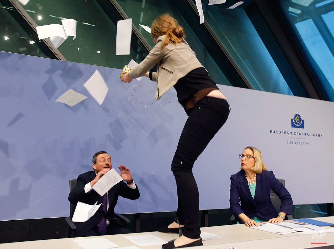 An activist stands on the table of the podium throwing paper at ECB President Mario Draghi, left, as Christine Graeff, Director General of Communications, looks on during a press conference of the European Central Bank, ECB, in Frankfurt, Germany, Wednesday, April 15, 2015. (AP Photo/Michael Probst)