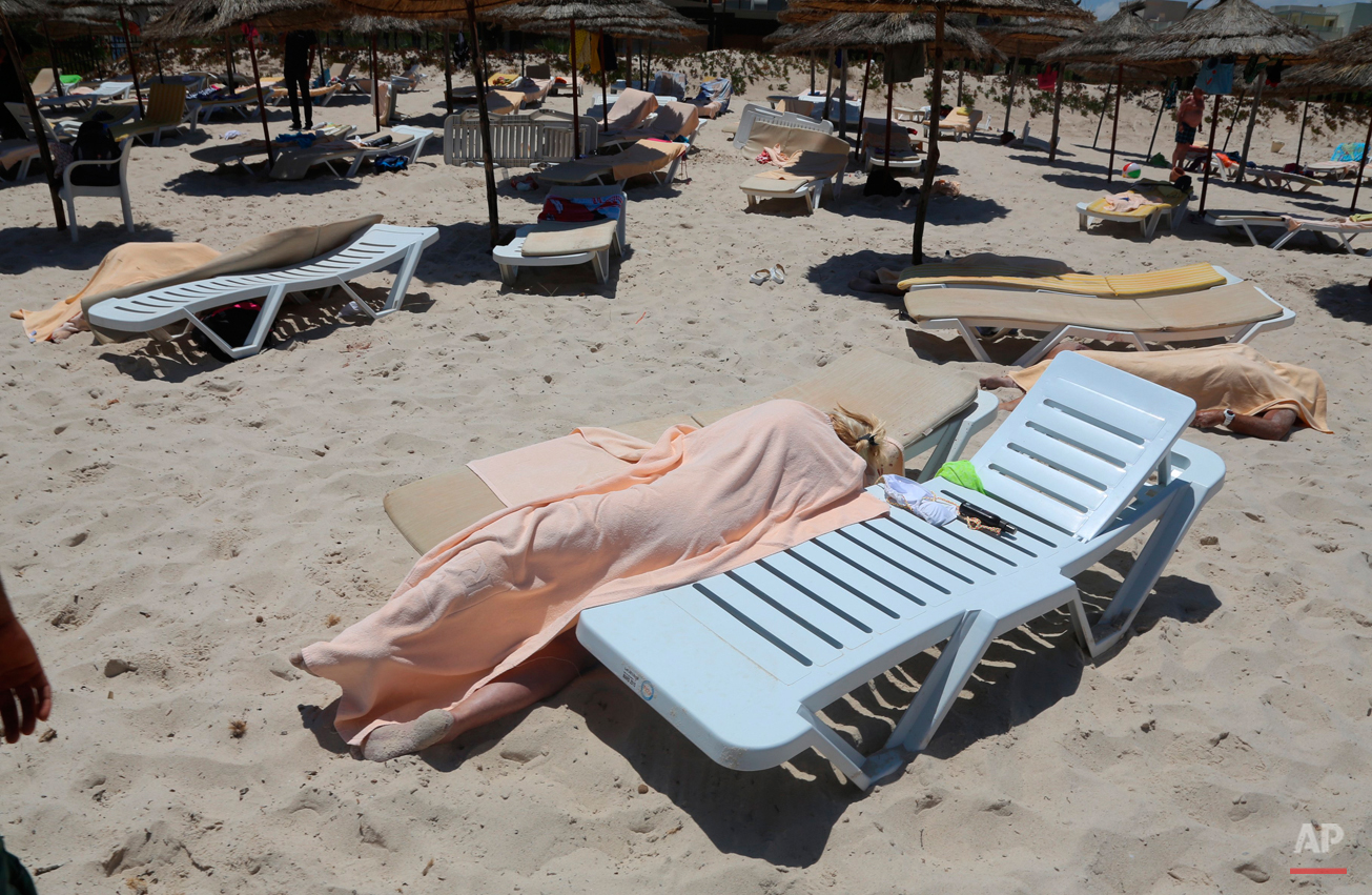Bodies are covered on a Tunisian beach, in Sousse, Friday June 26, 2015. A man unfurled an umbrella and pulled out a Kalashnikov, opening fire on European sunbathers in an attack that killed at least 28 people at the beach resort in one of three deadly attacks from Europe to the Middle East that followed a call to violence by Islamic State extremists. (Jawhara FM via AP)