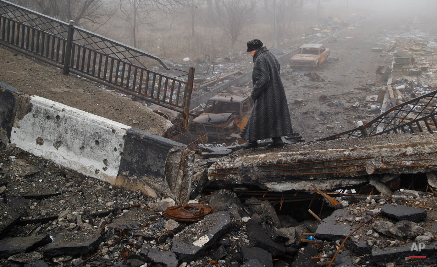 In this Sunday, March 1, 2015, photo, an elderly woman walks across a destroyed bridge, which has collapsed over the road to the airport, the scene of heavy fighting, in Donetsk, Ukraine.  (AP Photo/Vadim Ghirda)