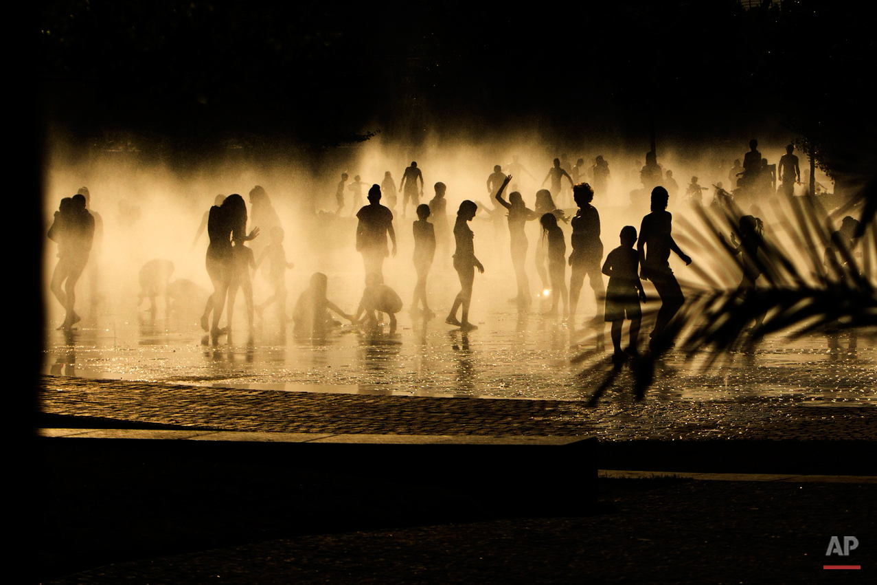 People cool down in a fountain beside Manzanares river in Madrid, Spain, Tuesday, June 30, 2015. Weather stations across Spain are warning people to take extra precautions as a heat wave engulfs much of the country, increasing the risk of wildfires. The country's meteorological agency says a mass of hot air originating in Africa is moving northwards, bringing temperatures reaching 40 Celsius (104 Fahrenheit). (AP Photo/Andres Kudacki)