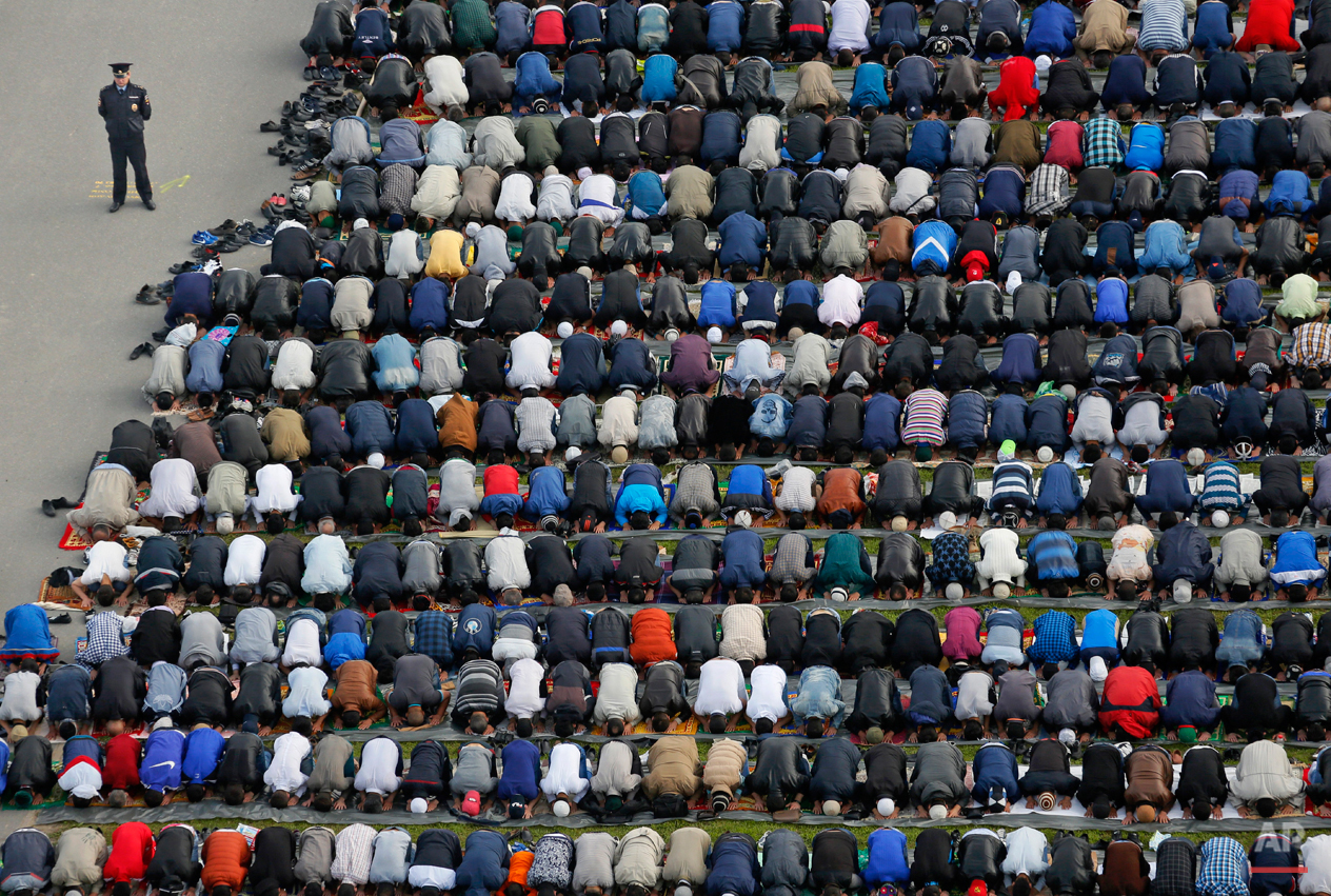 A policeman stands guard as Muslims take part in Eid al-Fitr prayers at a mosque in St. Petersburg, Russia, Friday, July 17, 2015. Millions of Muslims across the world are celebrating the Eid al-Fitr holiday, which marks the end of the month-long fast of Ramadan. (AP Photo/Dmitry Lovetsky)