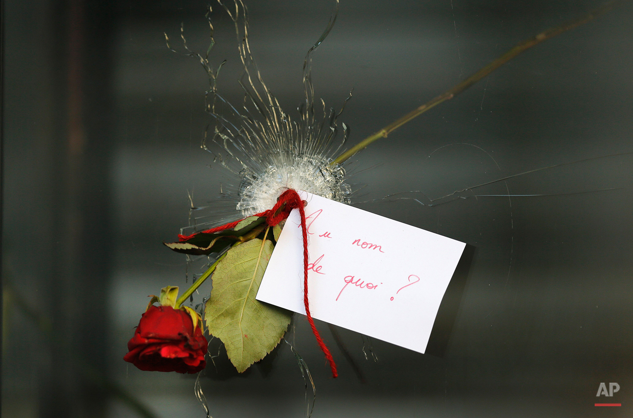 """A message that reads: """"In the name of what?"""" and a rose is placed through a bullet hole in a window at the restaurant on Rue de Charonne, Paris, Sunday, Nov. 15, 2015, where attacks took place on Friday. The Islamic State group claimed responsibility for Friday's attacks on a stadium, a concert hall and Paris cafes that left more than 120 people dead and over 350 wounded. (AP Photo/Frank Augstein)"""