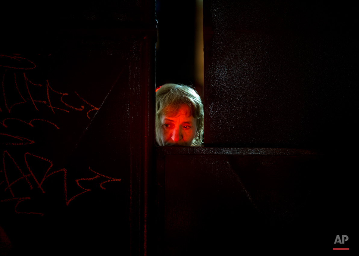 A woman face is lit by candles placed outside the Colectiv nightclub as she peers from behind the metal gate leading to the club in Bucharest, Romania, Monday, Nov. 2, 2015.  The owners of the Colectiv nightclub were questioned by prosecutors Monday in connection with a fire that engulfed a nightclub Friday night, causing a stampede to a single exit door of the basement club and leaving tens of people dead and many more injured. (AP Photo/Vadim Ghirda)