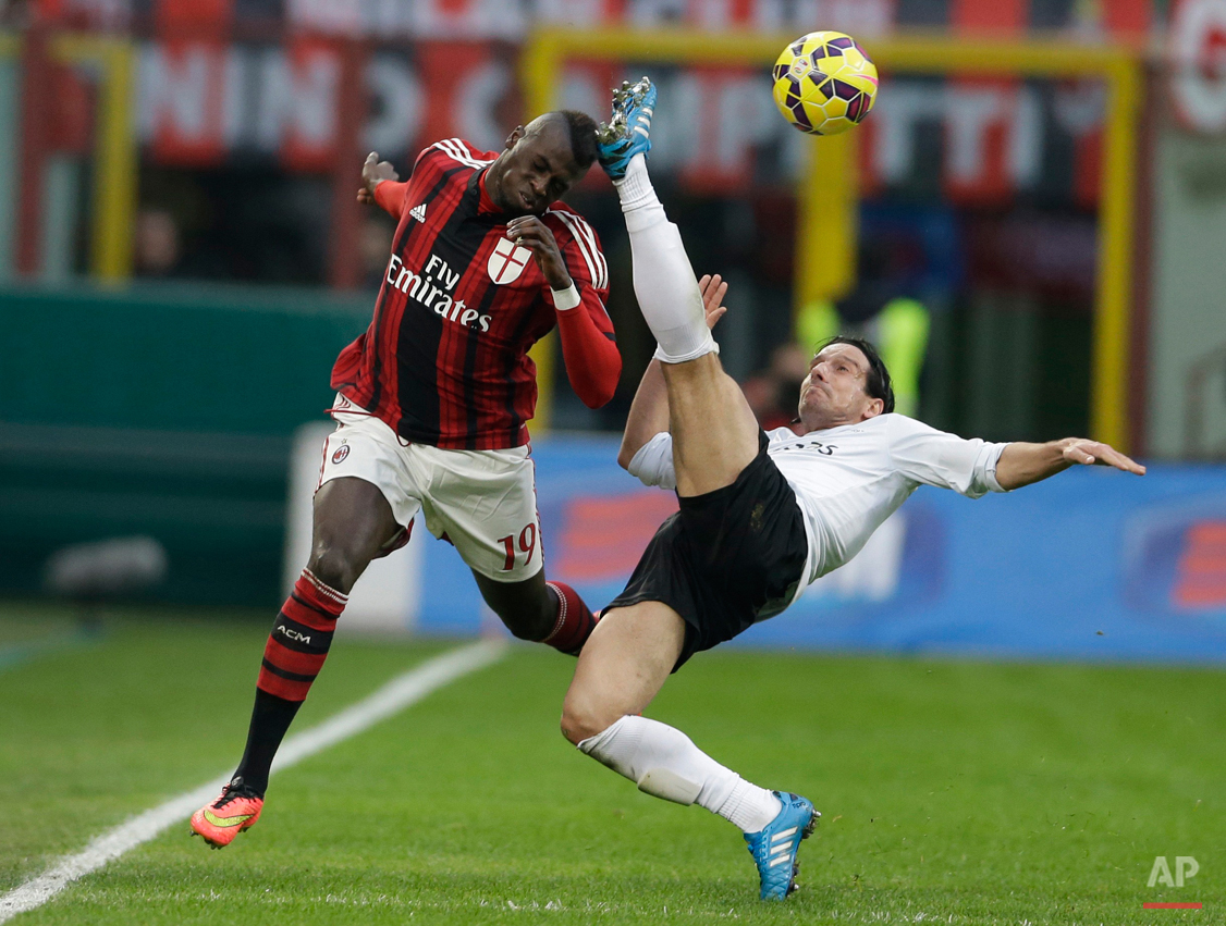 In this Jan. 18, 2015 photo, AC Milan's Mbaye Niang, left, challenges for the ball with Atalanta's Giuseppe Biava during a Serie A soccer match between AC Milan and Atalanta, at the San Siro stadium in Milan. (AP Photo/Luca Bruno)
