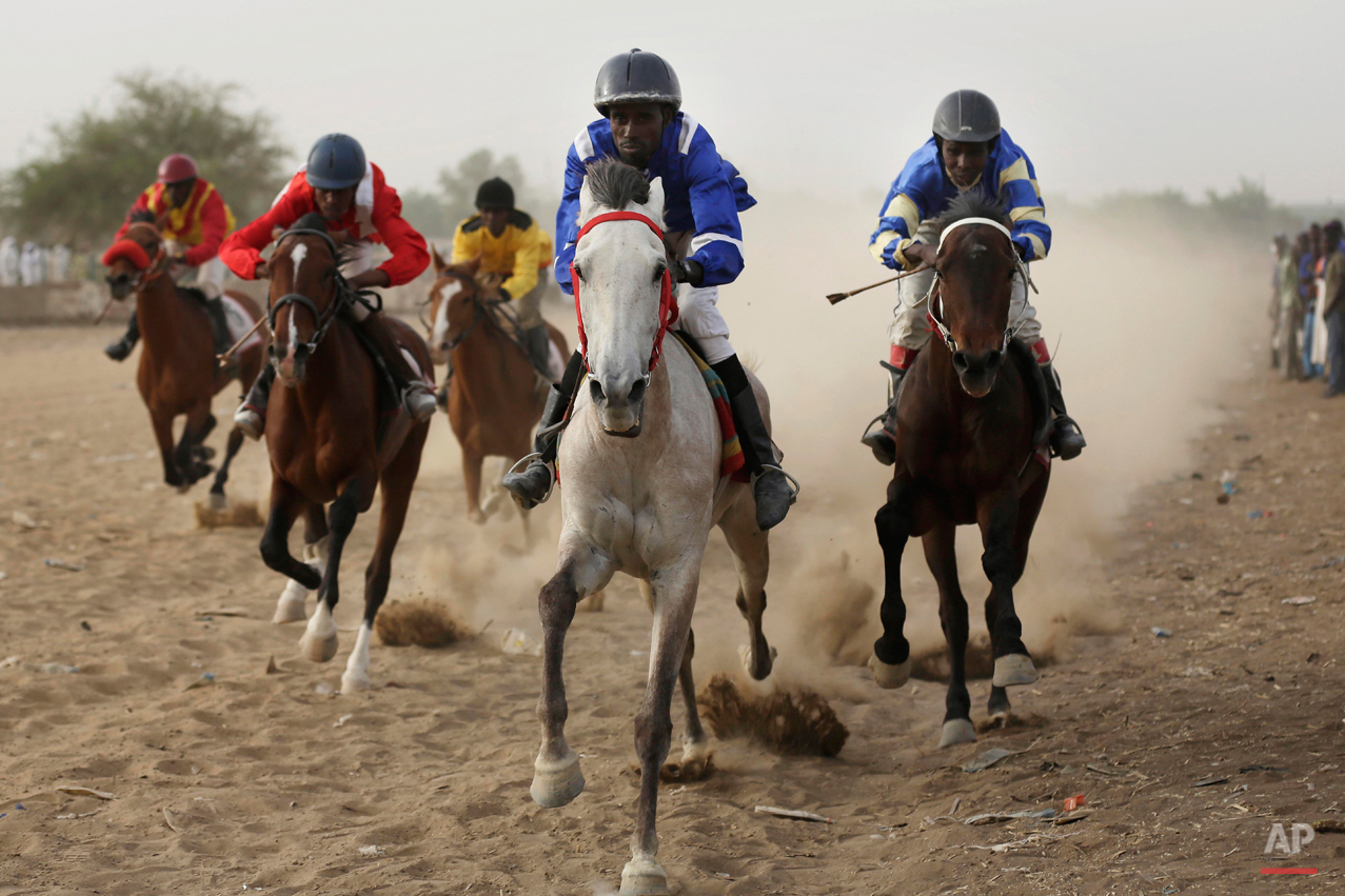 In this Sunday, March 15, 2015 photo, Chadian jockeys race to the finish line during an afternoon of races at the hippodrome in N'djamena, Chad. Horse races take place every Sunday, bringing hundreds of spectators willing to brave the excruciating heat to watch their favorite sport.(AP Photo/Jerome Delay)
