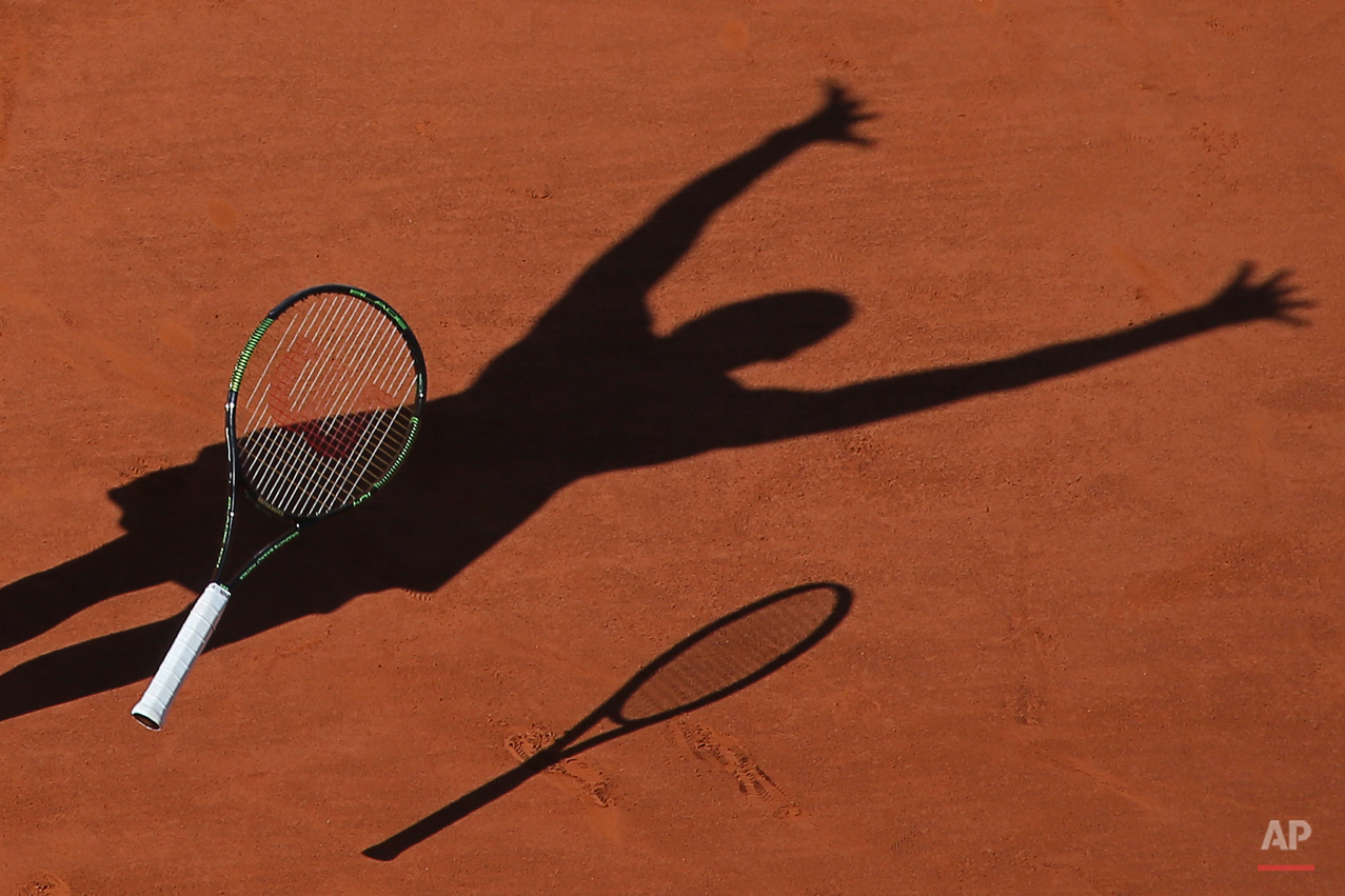 In this Saturday June 6, 2015 photo, Serena Williams of the U.S. casts a shadow on the clay as she drops her racket and celebrates winning the final of the French Open tennis tournament against Lucie Safarova of the Czech Republic in three sets, 6-3, 6-7, 6-2, at the Roland Garros stadium, in Paris, France. (AP Photo/David Vincent)