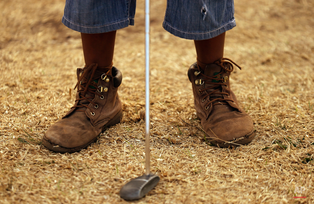 In this Thursday, July 16, 2015 photo ten-year-old Amohela Mokoena, plays a putt during a golf game at a park in Katlehong township, east of Johannesburg, South Africa. At first the township children only watched as their retired neighbour and former golf caddie, Wynand Morudu, hit a ball up and down the open field then soon they joined in, forming an amateur golf training school in the working class South African township. (AP Photo/Themba Hadebe)
