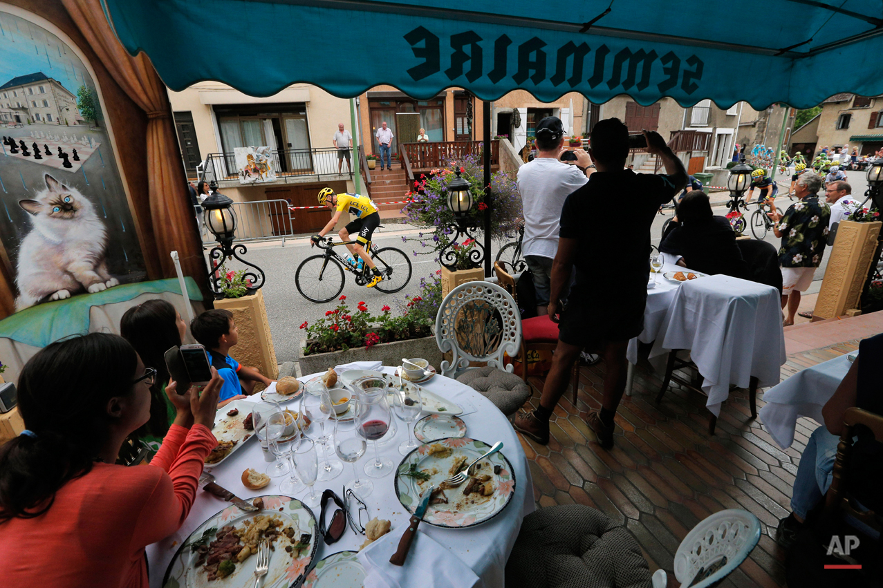 In this Thursday, July 23, 2015 file photo clients watch from the terrace of a restaurant as the pack with Britain's Chris Froome, wearing the overall leader's yellow jersey, passes during the eighteenth stage of the Tour de France cycling race over 186.5 kilometers (115.9 miles) with start in Gap and finish in Saint-Jean-de-Maurienne, France. (AP Photo/Christophe Ena)