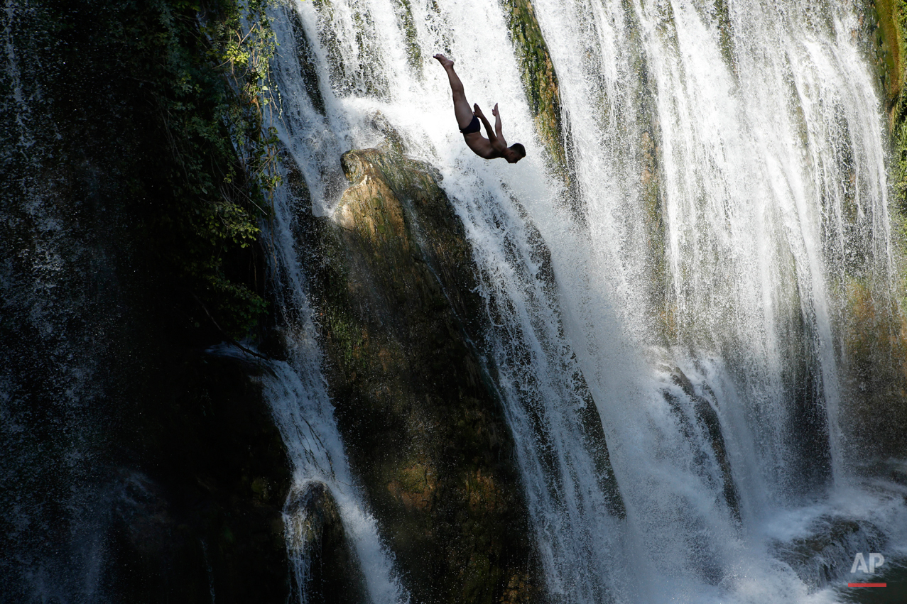 In this Aug. 1, 2015 photo a competitor dives during international waterfall jumping competition in the old town of Jajce, 250 kms west of Sarajevo, Bosnia.  Total of 25 competitors took part in this jumps from waterfall 20 meters high.(AP Photo/Amel Emric)
