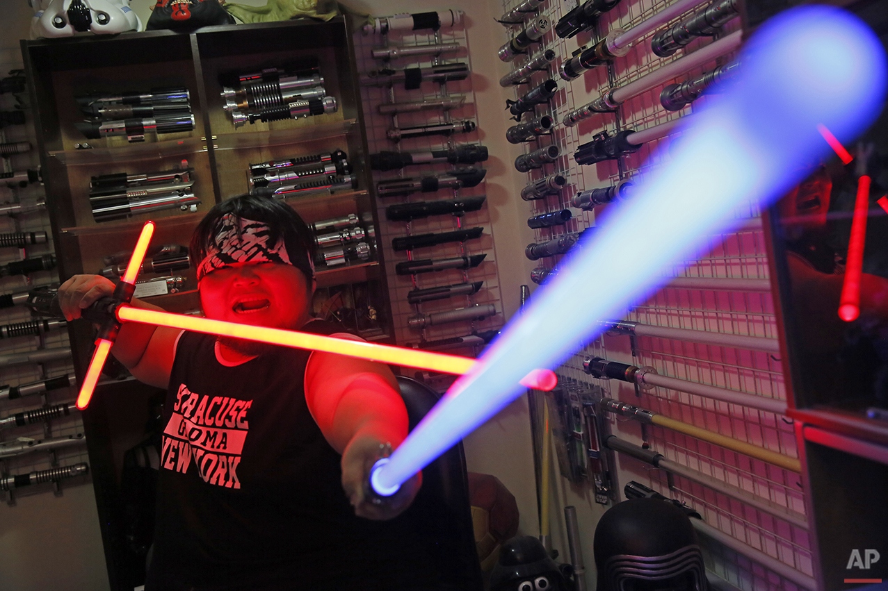 "In this Dec. 14, 2015, photo, 32-year-old Tsai Jung-chou, also known as ""Makoto Tsai"", poses with his handcrafted replicas of the Star Wars lightsaber at his home workshop in New Taipei City, Taiwan. A former optical engineer, Tsai now designs and fabricates his own versions of the iconic sci-fi weapon which he sells for up to $400 per model. (AP Photo/Wally Santana)"