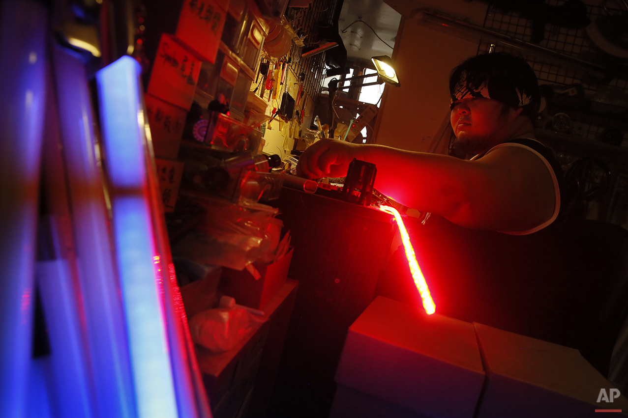 "In this Dec. 14, 2015, photo, 32-year-old Tsai Jung-chou, also known as ""Makoto Tsai"", upgrades a replica Star Wars lightsaber with his personally designed LEDs and sound card at his home workshop in New Taipei City, Taiwan. A former optical engineer, Tsai now designs and fabricates his own versions of the iconic sci-fi weapon which he sells for up to $400 per model. (AP Photo/Wally Santana)"