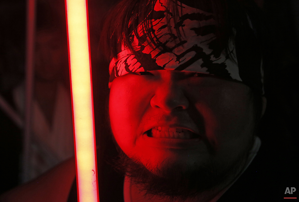 "In this Dec. 14, 2015, photo, 32-year-old Tsai Jung-chou, right, also known as ""Makoto Tsai"", poses with his handcrafted replica of the Star Wars lightsaber at his home workshop in New Taipei City, Taiwan. A former optical engineer, Tsai now designs and fabricates his own versions of the iconic sci-fi weapon which he sells for up to $400 per model. (AP Photo/Wally Santana)"