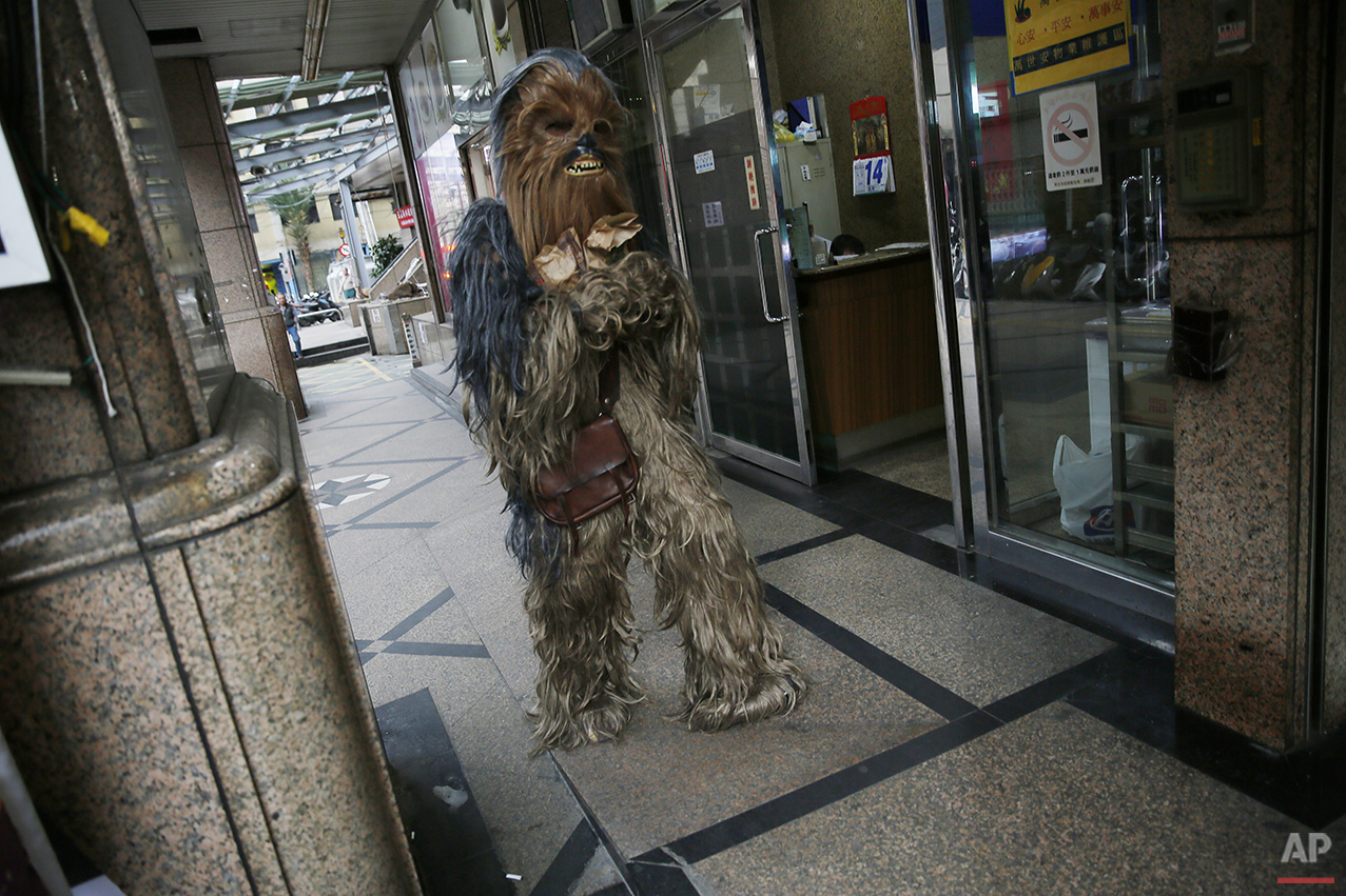 "In this Dec. 14, 2015, photo, a Star Wars fan dressed as ""Chewbacca"" carries bags of fast food after visiting a restaurant in the neighborhood of 32-year-old Tsai Jung-chou, also known as ""Makoto Tsai"", who makes replica lightsabers at his home workshop in New Taipei City, Taiwan. A former optical engineer, Tsai now designs and fabricates his own versions of the iconic sci-fi weapon which he sells for up to $400 per model. (AP Photo/Wally Santana)"