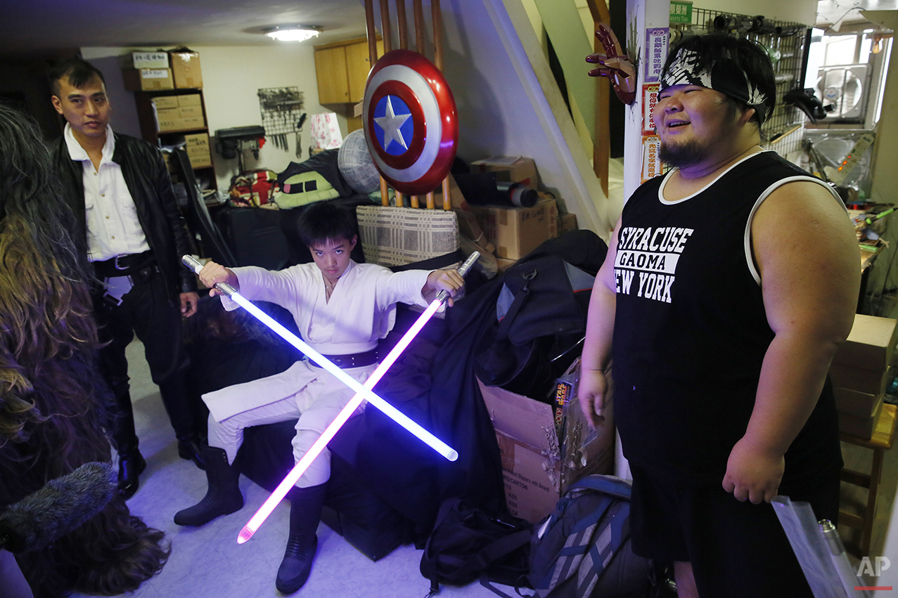 "In this Dec. 14, 2015, photo, 32-year-old Tsai Jung-chou, right, also known as ""Makoto Tsai"", stands with his friends dressed as Star Wars characters and holding his handcrafted replicas of the Star Wars lightsaber at his home workshop in New Taipei City, Taiwan. A former optical engineer, Tsai now designs and fabricates his own versions of the iconic sci-fi weapon which he sells for up to $400 per model. (AP Photo/Wally Santana)"