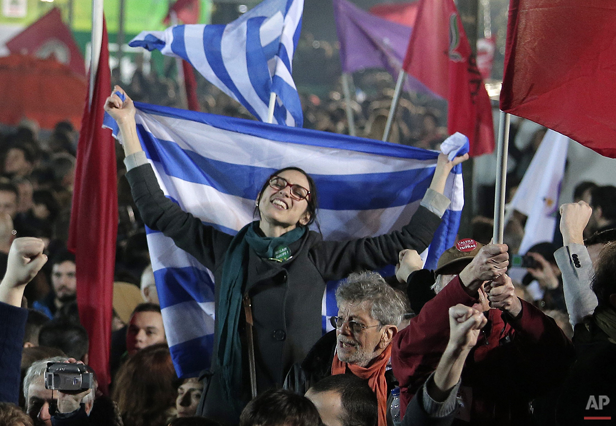In this Sunday, Jan. 25, 2015, a supporter of Alexis Tsipras leader of Syriza left-wing party holds the Greek flag after his election victory outside Athens University Headquarters. Anyone hoping Greece might finally have a quiet year was quickly disappointed in 2015. Brinkmanship with bailout lenders brought the country a half-step from financial collapse and eurozone exit, while Greece was at the center of Europe's worst refugee crisis since World War II. (AP Photo/Lefteris Pitarakis)