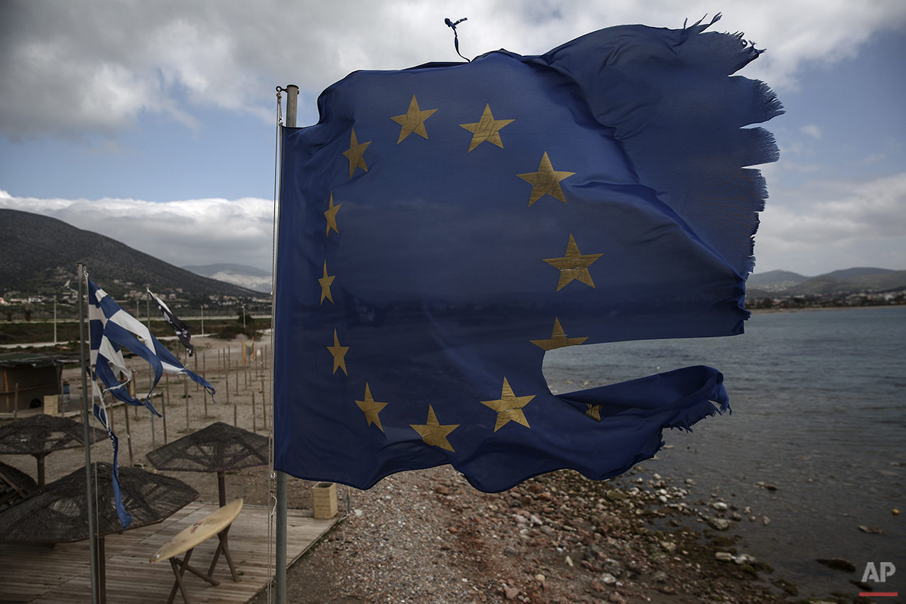 In this photo taken on Monday, March 16, 2015, ruined EU and Greek flags fly in tatters from a flag pole at a beach at Anavissos village, southwest of Athens. Anyone hoping Greece might finally have a quiet year was quickly disappointed in 2015. Brinkmanship with bailout lenders brought the country a half-step from financial collapse and eurozone exit, while Greece was at the center of Europe's worst refugee crisis since World War II. (AP Photo/Yorgos Karahalis)