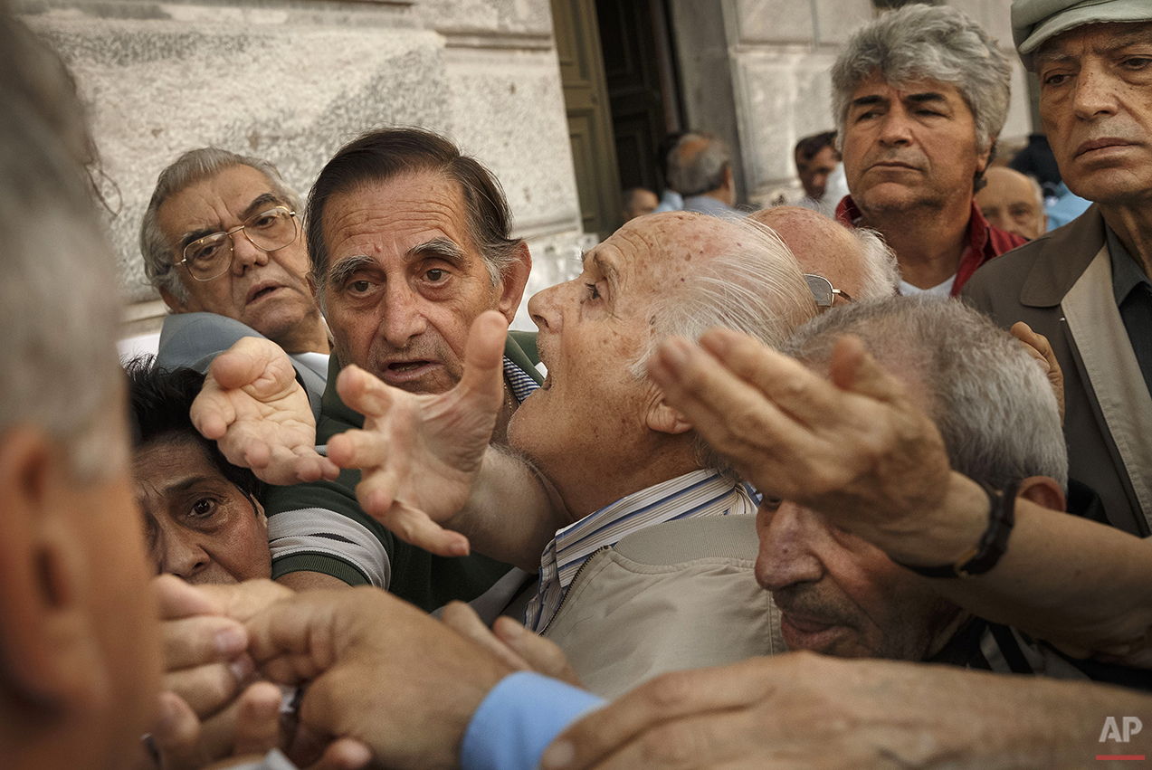 In this photo taken on Wednesday, July 1, 2015, pensioners try to get a number to enter inside a bank in Athens. Anyone hoping Greece might finally have a quiet year was quickly disappointed in 2015. Brinkmanship with bailout lenders brought the country a half-step from financial collapse and eurozone exit, while Greece was at the center of Europe's worst refugee crisis since World War II. (AP Photo/Daniel Ochoa de Olza)