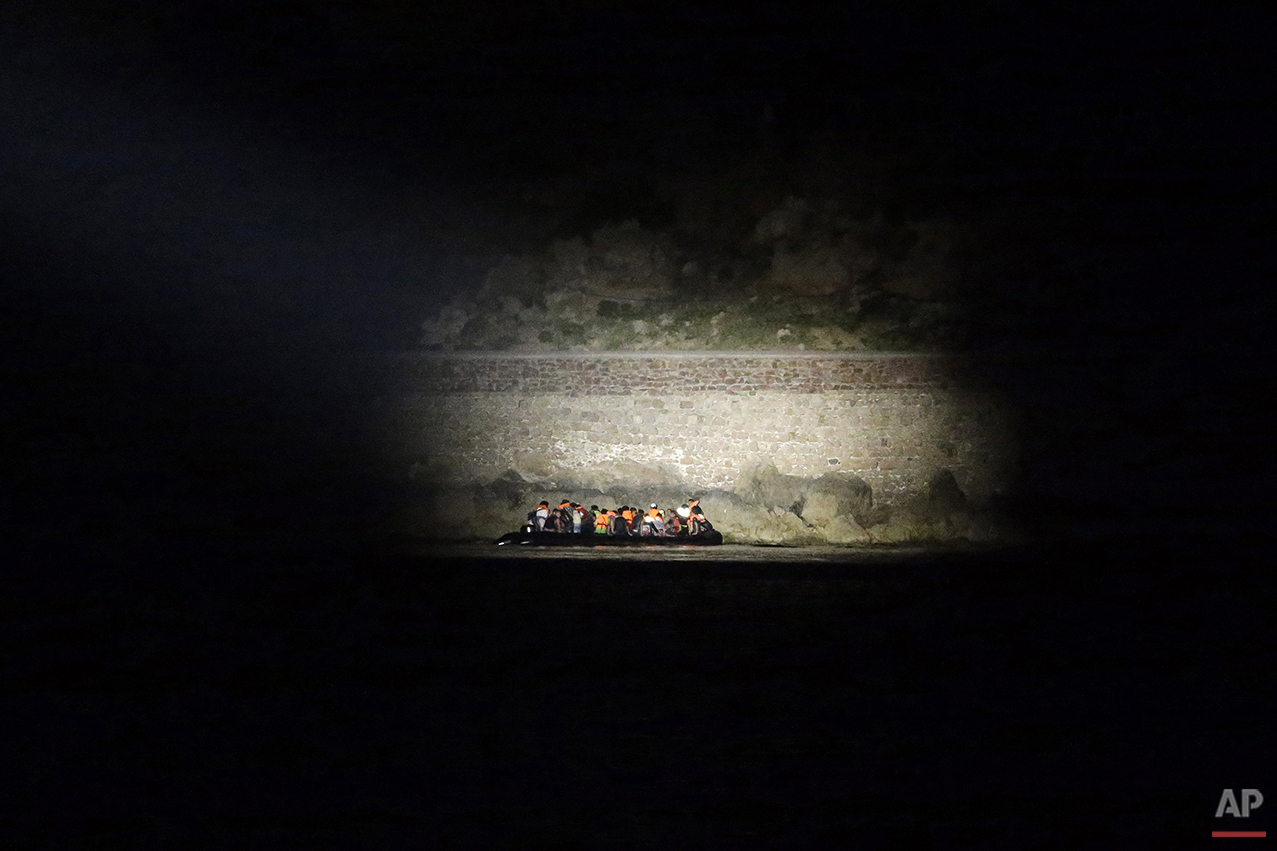 In this photo taken on Thursday, June 18, 2015, a Greek coast guard vessel uses a light to spot migrants arrive on an overcrowded dinghy from the Turkish coast during a patrol operation near the port of Mytilene on the Greek island of Lesvos. Anyone hoping Greece might finally have a quiet year was quickly disappointed in 2015. Brinkmanship with bailout lenders brought the country a half-step from financial collapse and eurozone exit, while Greece was at the center of Europe's worst refugee crisis since World War II. (AP Photo/Thanassis Stavrakis)