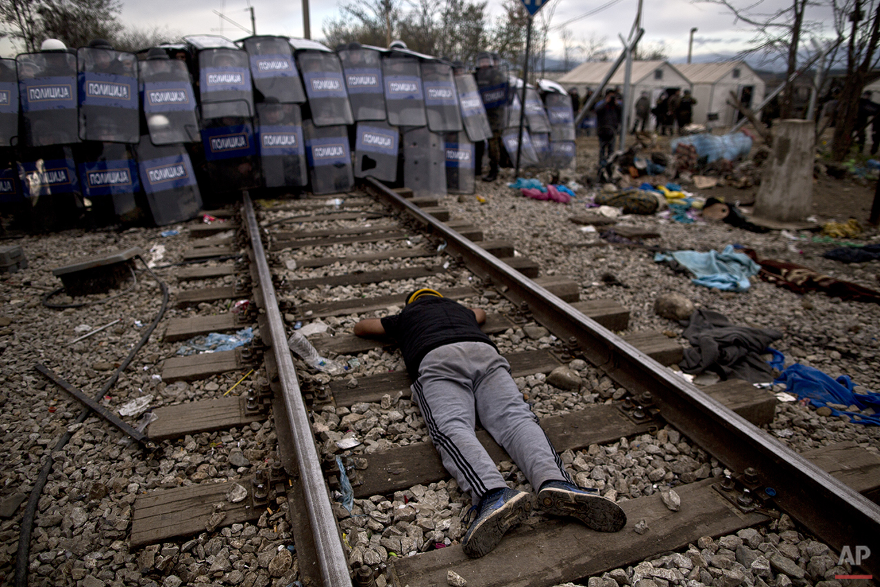 In this photo taken on Saturday, Nov. 28, 2015, a migrant lies on the railway track in front of Macedonian policemen during clashes at the Greek-Macedonian border, near the northern Greek village of Idomeni. Anyone hoping Greece might finally have a quiet year was quickly disappointed in 2015. Brinkmanship with bailout lenders brought the country a half-step from financial collapse and eurozone exit, while Greece was at the center of Europe's worst refugee crisis since World War II. (AP Photo/Muhammed Muheisen)