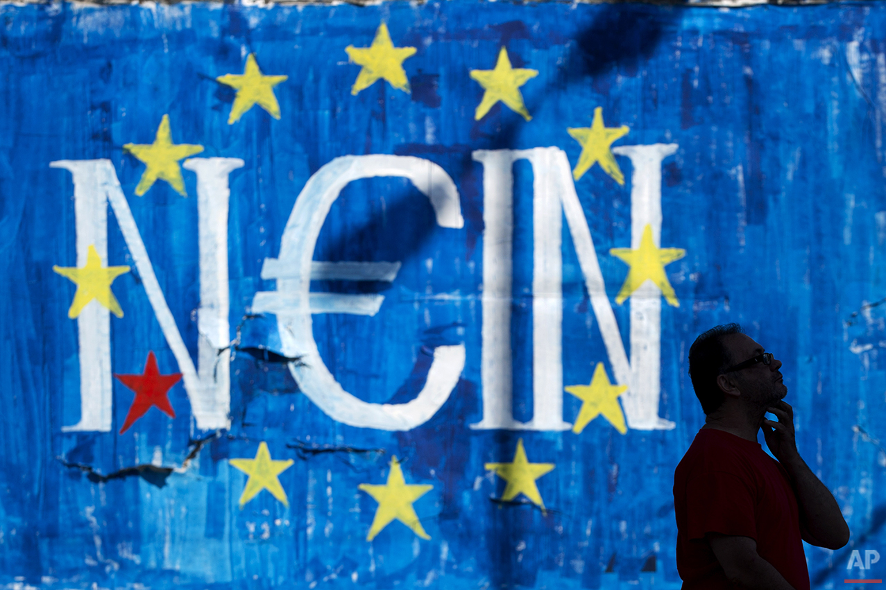 In this photo taken on Sunday, June 28, 2015, a man walks past a graffiti made by street artist N_Grams  that  read ''NO'' in German but also ''YES, IN'' in Greek language in Athens. Anyone hoping Greece might finally have a quiet year was quickly disappointed in 2015. Brinkmanship with bailout lenders brought the country a half-step from financial collapse and eurozone exit, while Greece was at the center of Europe's worst refugee crisis since World War II. (AP Photo/Petros Giannakouris)