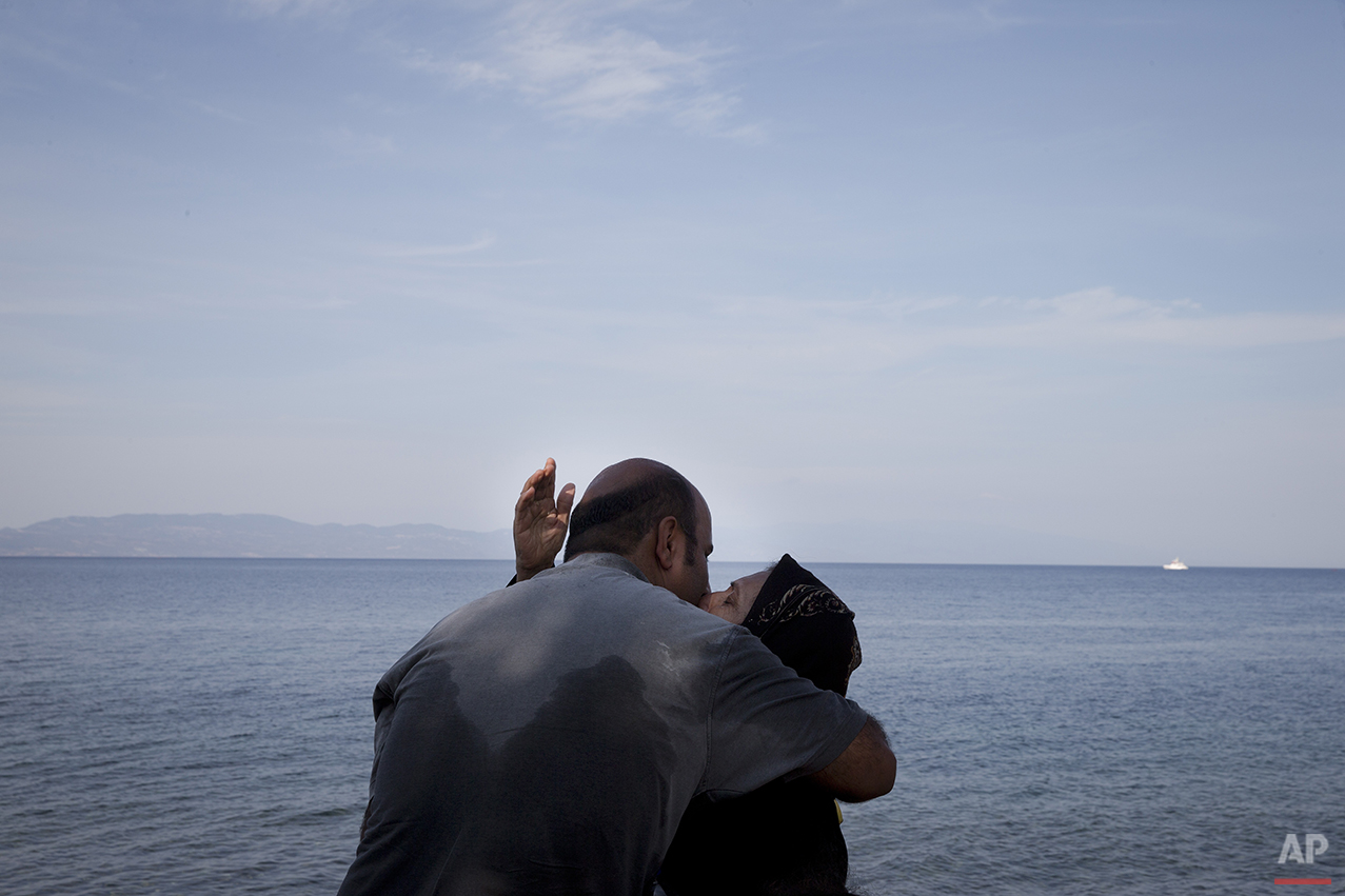 In this photo taken on Wednesday, Sept. 9, 2015, a woman and a man kiss after their arrival on a dinghy with other migrants and refugees from the Turkish coast to the northeastern Greek island of Lesbos. Anyone hoping Greece might finally have a quiet year was quickly disappointed in 2015. Brinkmanship with bailout lenders brought the country a half-step from financial collapse and eurozone exit, while Greece was at the center of Europe's worst refugee crisis since World War II. (AP Photo/Petros Giannakouris)