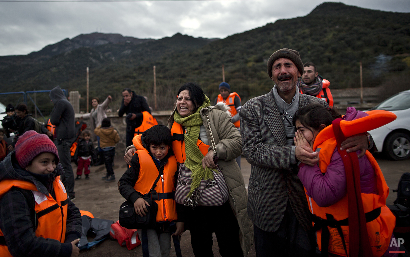 In this Thursday, Dec. 3, 2015 photo, Yazidi refugee Samir Qasu, 45, right, from Sinjar, Iraq, and his wife Bessi, 42, cry while embracing their children, Dunia, 13, and Dildar, 10, shortly after arriving on a vessel from the Turkish coast to the northeastern Greek island of Lesbos. The Oasus, left the Turkish coast before dawn on Dec. 3 bound for the island of Lesbos, the first port of  EU call for nearly 400,000 asylum seekers this year.  (AP Photo/Muhammed Muheisen)