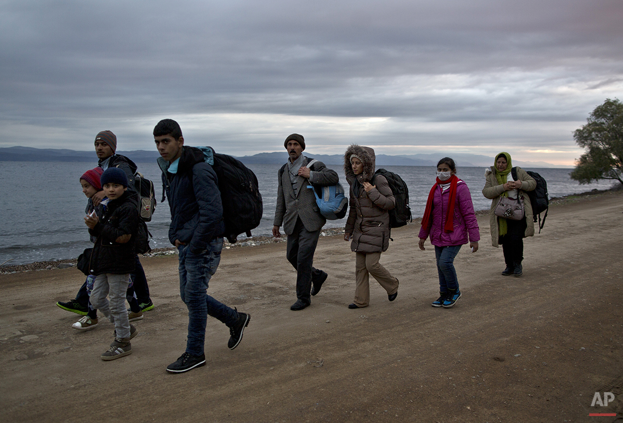 In this Thursday, Dec. 3, 2015 photo, Yazidi refugee Samir Qasu, 45, from Sinjar, Iraq, and his wife Bessi, 42, their two daughters Delphine, 18, Dunia 13, and their two sons Dilshad, 17, and Dildar, 10, walk toward a gathering point to board a bus to a registration center, after arriving on a vessel from the Turkish coast to the northeastern Greek island of Lesbos. The Qasus, left the Turkish coast before dawn on Dec. 3 bound for the island of Lesbos, the first port of EU call for nearly 400,000 asylum seekers this year.  (AP Photo/Muhammed Muheisen)