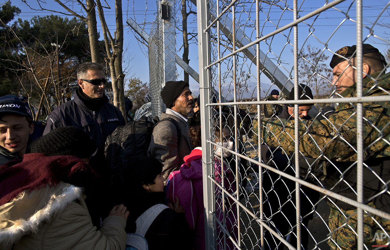In this Saturday, Dec. 5, 2015 photo, Yazidi refugee Samir Qasu, 45, center, from Sinjar, Iraq, and his family approach Macedonian army officers as they cross a fence at the Greek-Macedonian border, near the northern Greek village of Idomeni. Within two days of arriving on Lesbos, the Qasus had traveled by midnight ferry from Lesbos to Athens and then by bus to Greece's northern border with Macedonia.  (AP Photo/Muhammed Muheisen)