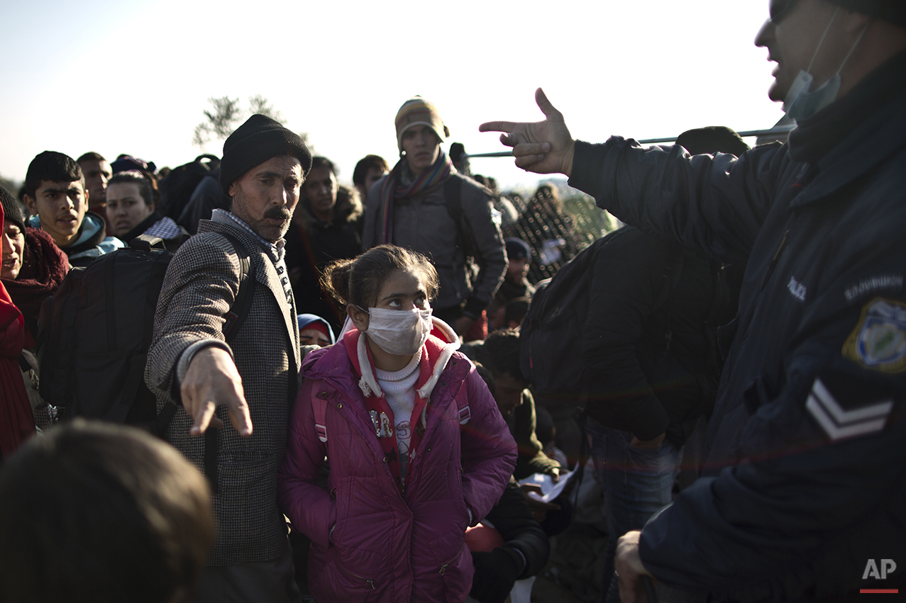 In this Saturday, Dec. 5, 2015 photo, Yazidi refugee Samir Qasu, 45, center, from Sinjar, Iraq, and his  daughter Dunia, 13, gestures to a Greek police officer while he and his family and other refugees and migrants wait to be permitted to cross the Greek-Macedonian border, near the northern Greek village of Idomeni.  Within two days of arriving on Lesbos, the Qasus had traveled by midnight ferry from Lesbos to Athens and then by bus to Greece's northern border with Macedonia.  (AP Photo/Muhammed Muheisen)