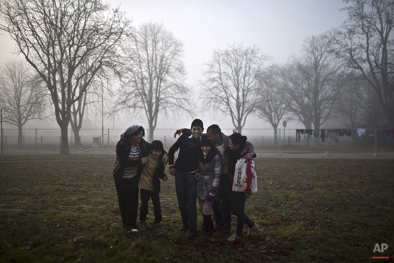 In this Thursday, Dec. 10, 2015 photo, Qasu family, a Yazidi refugee family from Sinjar, Iraq, laugh shortly before posing for a picture outside their new temporary home at Patrick Henry Village, in Heidelberg, Germany. (AP Photo/Muhammed Muheisen)