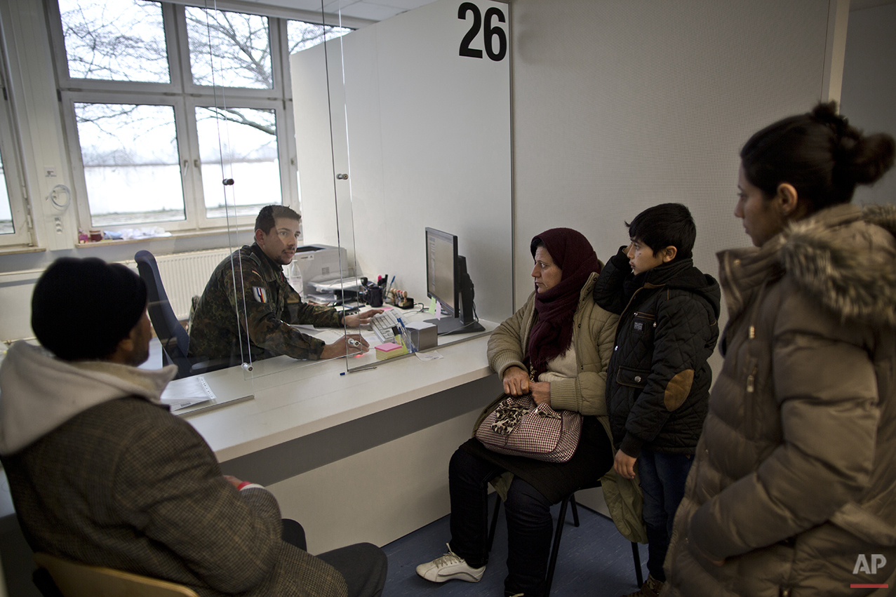 In this Wednesday, Dec. 9, 2015 photo, a German army soldier fills in the details of Qasu family, a Yazidi refugee family from Sinjar, Iraq, as part of their asylum seeking process at the Central Registration Centre in Patrick Henry Village in Heidelberg, Germany. (AP Photo/Muhammed Muheisen)