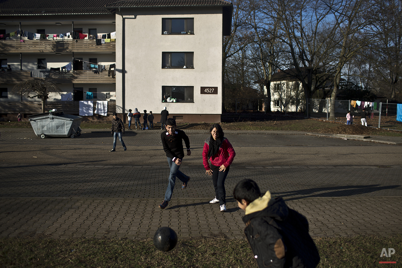 In this Thursday, Dec. 10, 2015 photo, Dilshad Qasu, 17, center, a Yazidi refugee from Sinjar, Iraq, plays football with his sister Delphine, 18, and his brother Dildar, 10, near their new temporary home at Patrick Henry Village, in Heidelberg, Germany. (AP Photo/Muhammed Muheisen)