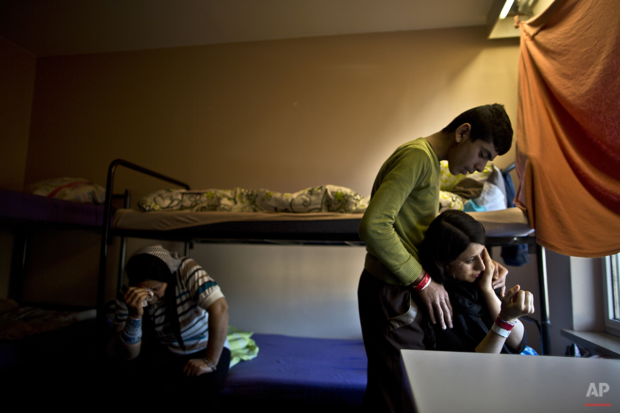 In this Thursday, Dec. 10, 2015 photo, Delphine Qasu, 18, right, a Yazidi refugee from Sinjar, Iraq, is comforted by her brother Dilshad, 17, while crying after talking about their journey to reach Germany, at their new temporary home at Patrick Henry Village, in Heidelberg, Germany. The Qasus do not normally cry, but this felt nothing like normal. Like hundreds of thousands before them and untold more to come, the Iraqi family had just completed a disorienting dash across Europe and found refuge in Germany. (AP Photo/Muhammed Muheisen)