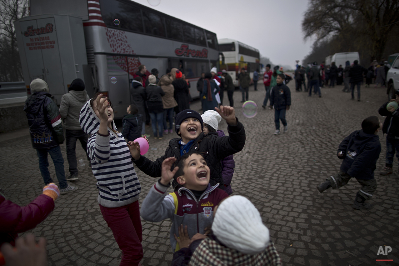 In this Sunday, Dec. 6, 2015 photo, Dildar Qasu, 10, center, a Yazidi refugee from Sinjar, Iraq, and other refugee children from Syria and Afghanistan chase bubbles released by a volunteer, while waiting with their families to be transported by a bus to the train station in Sid where Serbian authorities load trains with refugees to Croatia, in Adasevci, Serbia. (AP Photo/Muhammed Muheisen)