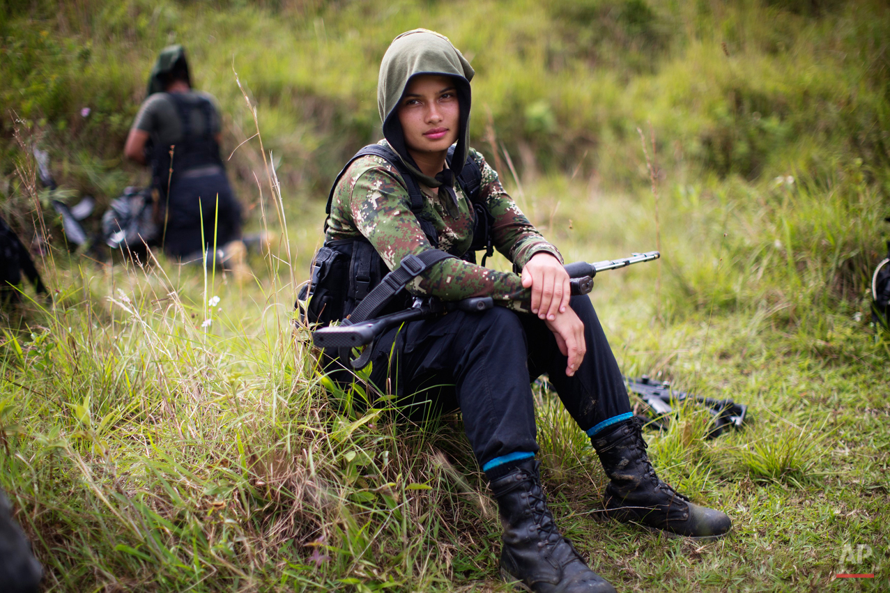 In this Jan. 6, 2016 photo, Juliana, a 20-year-old rebel fighter for the 36th Front of the Revolutionary Armed Forces of Colombia, or FARC, rests from a trek in the northwest Andes of Colombia, in Antioquia state. Like many of her comrades in arms, her path to the FARC was born as much from personal tragedy as political ideology. In her case, she fled an impoverished home at age 16 and followed in the footsteps of an uncle after being raped by her stepfather. (AP Photo/Rodrigo Abd)