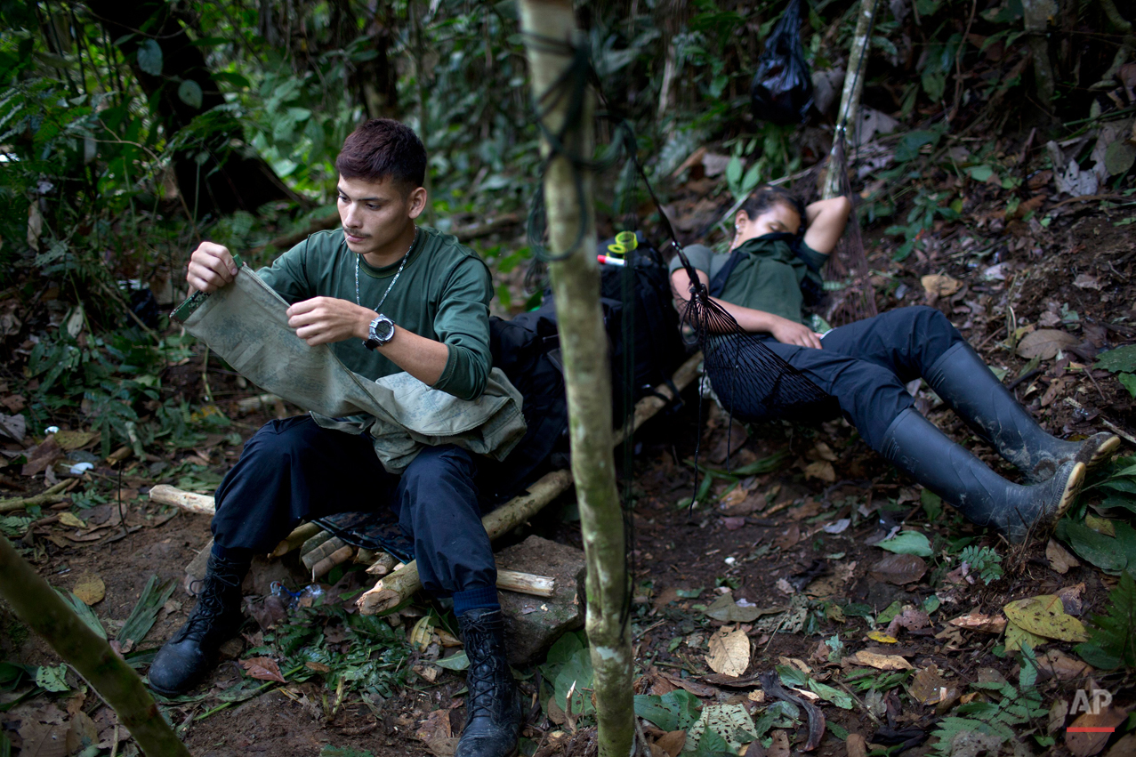 """In this Jan. 4, 2016 photo, Oscar, a rebel soldier for the 36th Front of the Revolutionary Armed Forces of Colombia, or FARC, mends a pair of pants while his """"socia"""" Gisell rests in a hammock, in a hidden camp in Antioquia state, in the northwest Andes of Colombia. Inside the rebel organization, the idea of """"socia"""" arose because the man cannot offer material wealth, so the girlfriends of the male rebels are referred to as a """"socia"""" or partner. (AP Photo/Rodrigo Abd)"""
