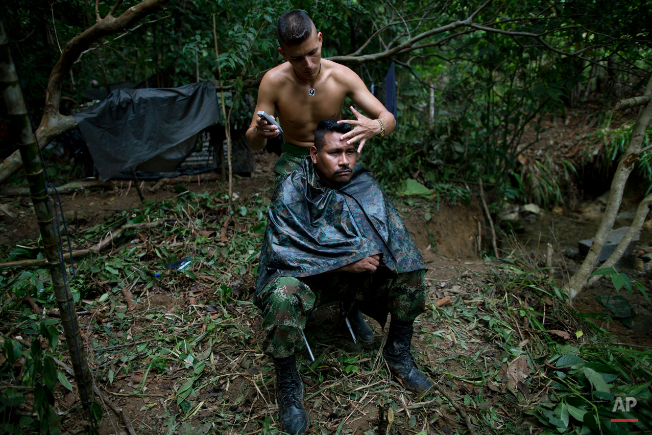 In this Jan. 5, 2016 photo, Alexis, a 24-year-old rebel fighter, trims the hair of Juan Pablo, a commander of the 36th Front of the Revolutionary Armed Forces of Colombia, or FARC, at their camp, hidden in the northwest Andes of Colombia, in Antioquia state. Now, after 25 years plotting ambushes and assembling land mines, peace is within reach and for the first time Juan Pablo is thinking about his own future outside this jungle hideout. (AP Photo/Rodrigo Abd)