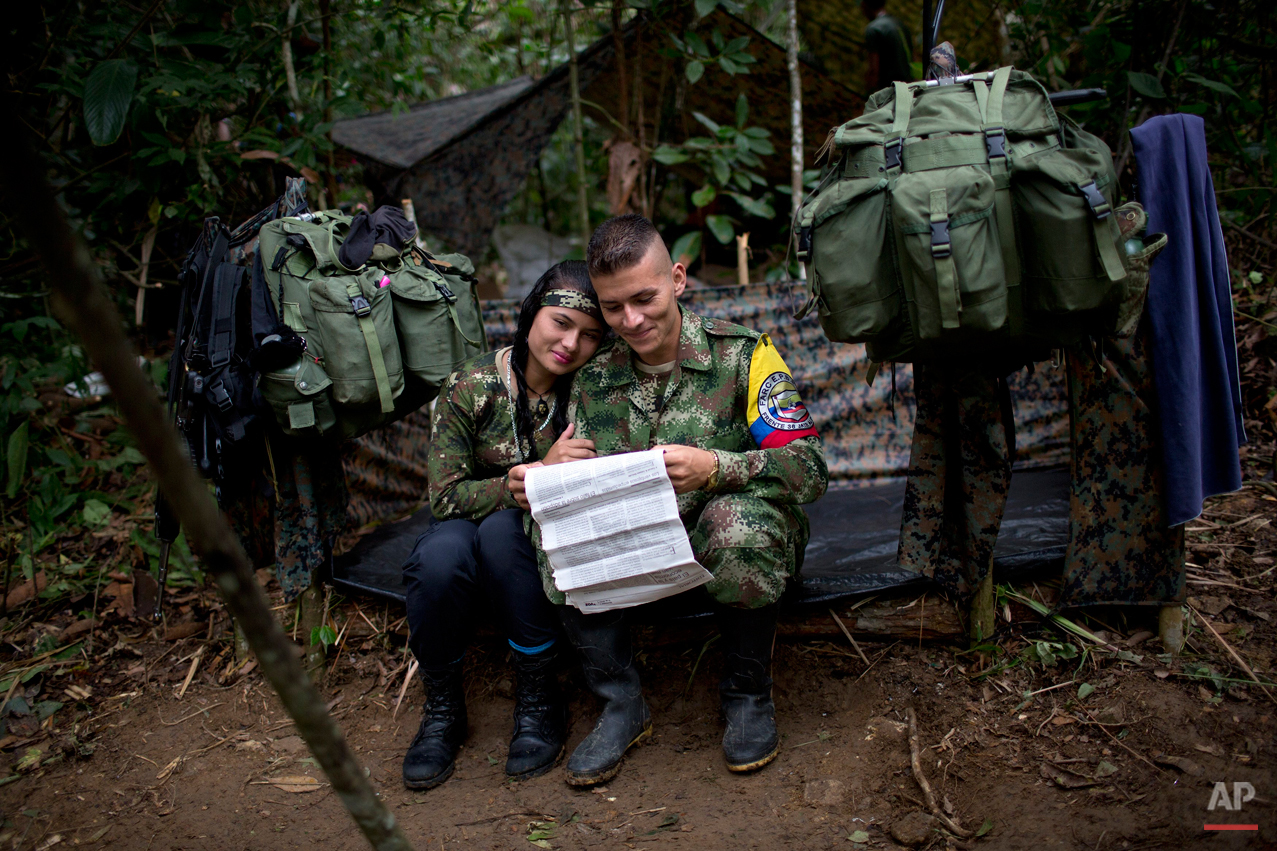 In this Jan. 4, 2016 photo, Juliana, a rebel soldier of the 36th Front of the Revolutionary Armed Forces of Colombia, or FARC, sits her with boyfriend Alexis, in their makeshift tent, inside their hidden camp in Antioquia, Colombia. ìInside the guerrilla we donít touch money, everything is given to us, from medicine to cigarettes. Thatís why thereís no dependency in which she expects me to provide for her as is common in Latin America,î explains Alexis. ìBetween us thereís just love.î (AP Photo/Rodrigo Abd)