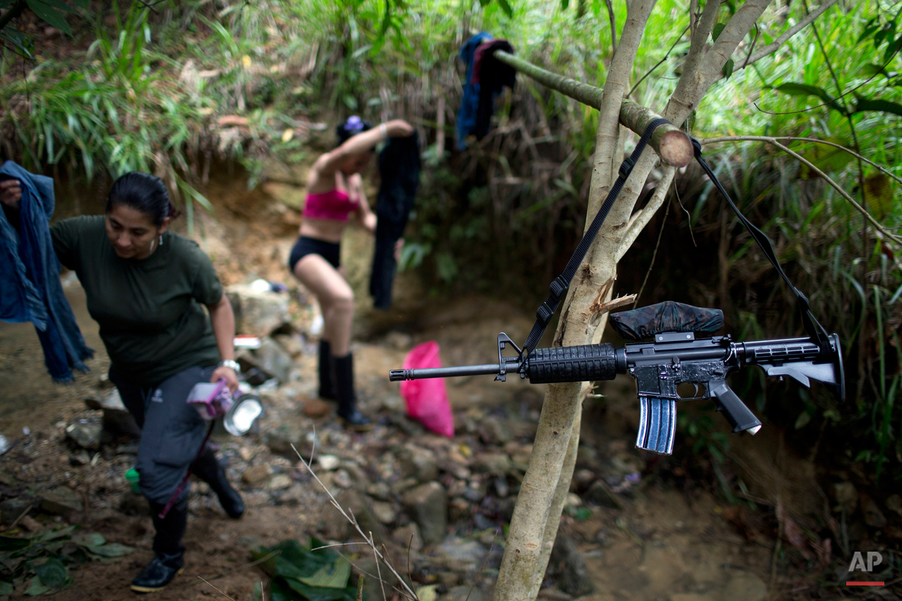 In this Jan. 4, 2016 photo, the weapon of a rebel fighter for the 36th Front of the Revolutionary Armed Forces of Colombia, or FARC, hangs from a branch serving as a makeshift clothesline, near a rebel camp, in Antioquia state, in the northwest Andes of Colombia. ìWeíll lay aside our weapons, like the accord says, but never hand them over,î says Juan Pablo, a commander of the 36th Front. (AP Photo/Rodrigo Abd)