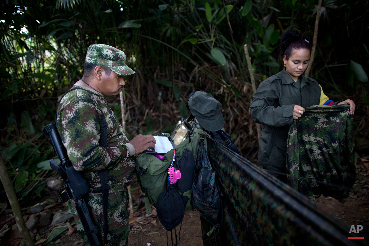 """In this Jan. 6, 2016 photo, Juan Pablo, a commander of the 36th Front of the Revolutionary Armed Forces of Colombia, or FARC,  works on his laptop, next to his girlfriend, 25-year-old rebel fighter Tania, at a hidden camp in Antioquia state, in the northwest Andes of Colombia. Tania says, """"If we sign the peace accords with the government, I would like to have two kids with Juan Pablo, study odontology and serve to the poor with my work."""" (AP Photo/Rodrigo Abd)"""