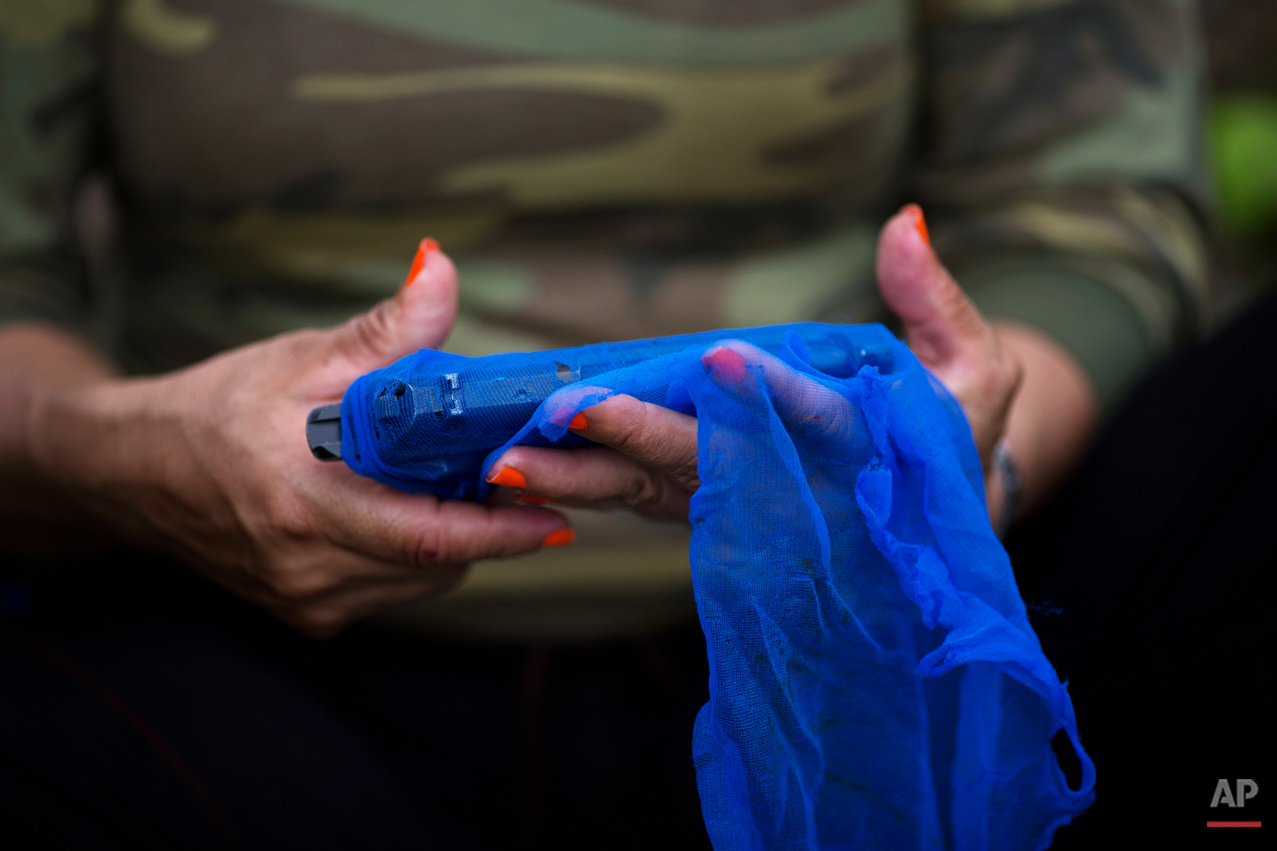 """In this Jan. 5, 2016 photo, Cindy, a rebel fighter for the 36th Front of the Revolutionary Armed Forces of Colombia, or FARC, wraps her gun in a mesh fabric, after a routine cleaning, as protection from humidity and rain, in a hidden camp in Antioquia state, in the northwest Andes of Colombia. Cindy is a field medic and she joined the guerrilla group when she was 18-years-old. """"If there is peace with the government, we will have to take up politics, teach the people and later reunite with family after so many years."""" she said. (AP Photo/Rodrigo Abd)"""