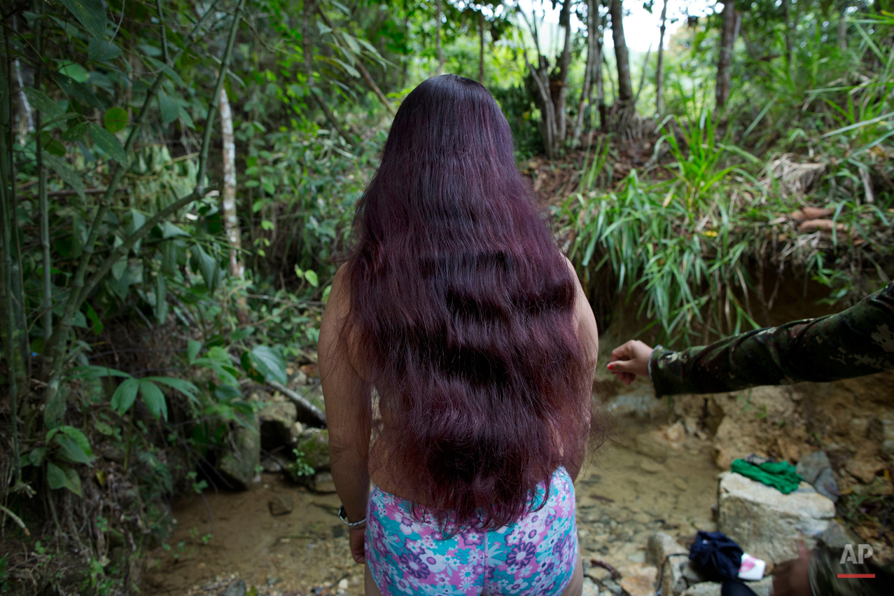 In this Jan. 5, 2016 photo, Marcela, a rebel soldier of the 36th Front of the Revolutionary Armed Forces of Colombia, or FARC, stands at the edge of a brook where she is preparing to bathe, near the guerrilla's group hidden camp in Antioquia state, in the northwest Andes of Colombia. The rebels inhabit an impenetrable forest with South Americaís only bear, venomous snakes and 20 species of exotic frogs. (AP Photo/Rodrigo Abd)
