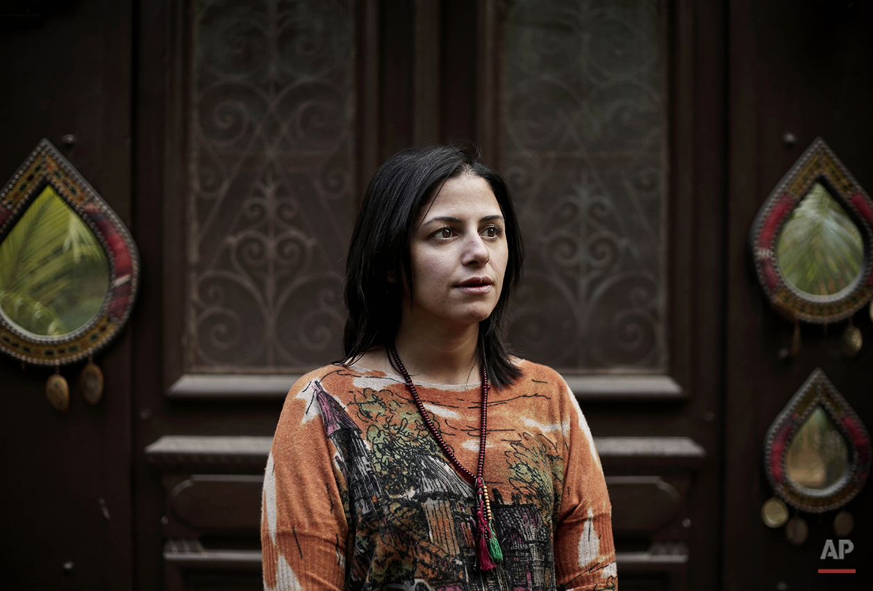 """Ghalia Ibrahim, a 37-year old dentist and triathlete, poses for a photograph inside her home, during the fifth anniversary of the 2011 uprising, in Cairo, Egypt, Monday, Jan. 25, 2016. """"I went on my bicycle to Tahrir Square and told the pro-regime people celebrating there that President Abdel-Fattah El-Sissi came to power because of the Jan. 25 revolution. I am very positive and hopeful that the country has a bright future. The people have to start working and stop criticizing,"""" says Ibrahim. (AP Photo/Nariman El-Mofty)"""