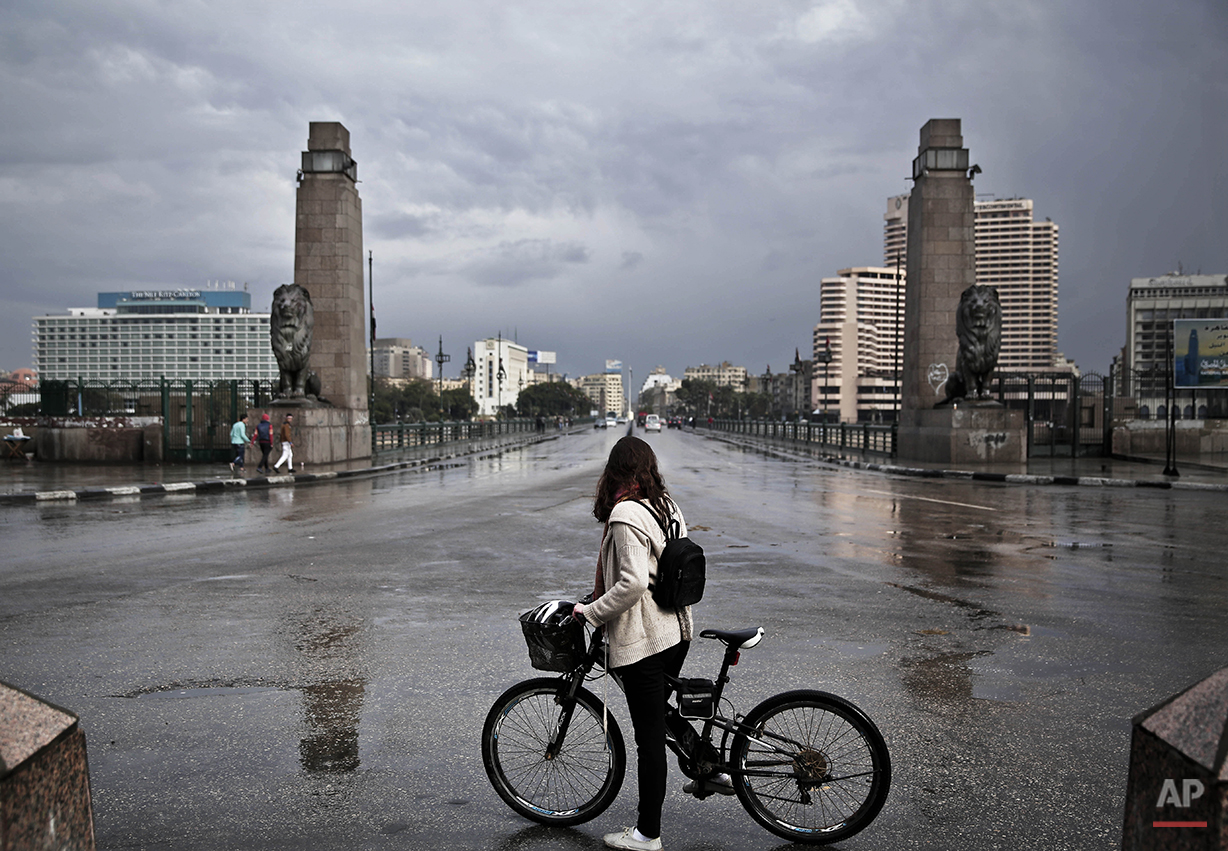 """A 27-year old Egyptian artist stops with her bicycle in front of the Kasr Al Nile bridge that leads to Tahrir Square, after making her way back from the square, during the fifth anniversary anniversary of the 2011 uprising, in Cairo, Egypt, Monday, Jan. 25, 2016. """"The anniversary of Jan. 25 2011 does not represent a single moment, but the start of an ongoing movement. This affected everything from the big things to the little things – such as giving me the push that I needed to ride my bike as a woman in Egypt. We have a different understanding now of public spaces and of our streets and that cannot be undone – no matter how hard they try,"""" says the young artist. (AP Photo/Nariman El-Mofty)"""