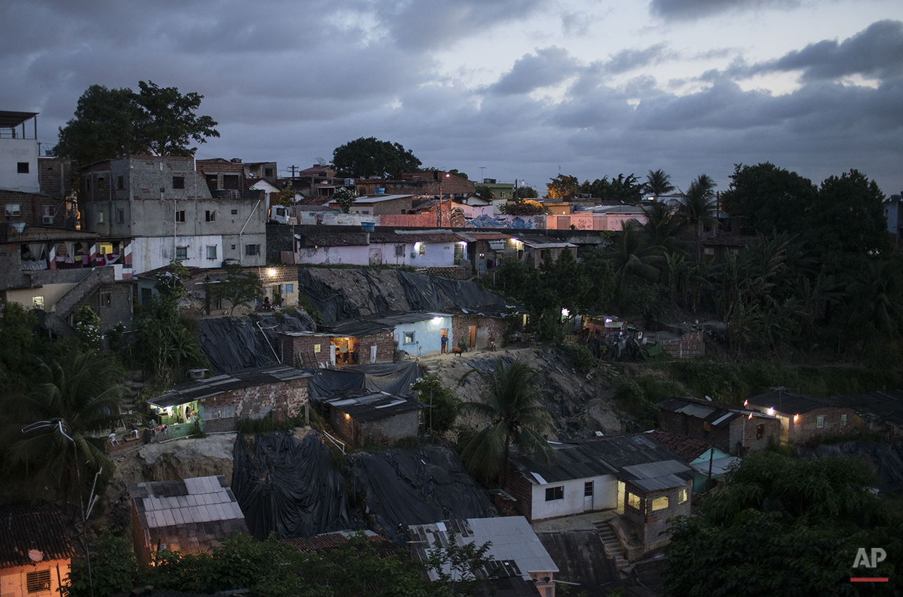 In this Jan. 27, 2016 photo, homes are lit by the setting sun in Ibura, one of the neighborhoods with the highest numbers of suspected cases of children born with microcephaly in Recife, Pernambuco state, Brazil. (AP Photo/Felipe Dana)