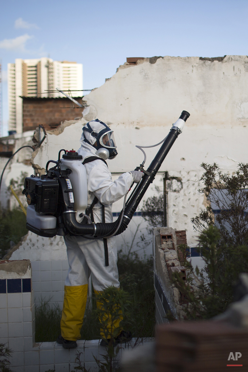 In this Jan. 26, 2016 photo, a municipal worker sprays insecticide to combat the Aedes aegypti mosquitoes that transmit the Zika virus, at the Imbiribeira neighborhood in Recife, Pernambuco state, Brazil. Brazil once succeeded in eliminating the Aedes, which is well adapted to humans, lives within people's homes and can breed in just a bottle cap of stagnant water. Massive eradication efforts in the 1940s and 1950s allowed the country to be declared free of the mosquito in 1958, but over the decades the insect returned (AP Photo/Felipe Dana)