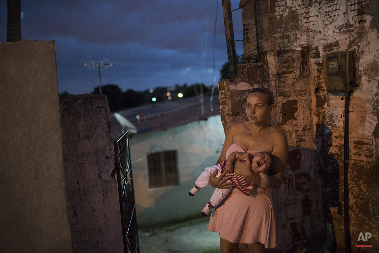 In this Jan. 27, 2016 photo, Gleyse Kelly da Silva, 27, holds her daughter Maria Giovanna, who was born with microcephaly, outside their house in Recife, Pernambuco state, Brazil. Mosquitoes have long been an inescapable part of the  slum in Recife's Apipucos neighborhood, where raw sewage flows in ditches, rain water from the frequent downpours in this equatorial city accumulates in fetid puddles, and the shores of a nearby pond are dotted with trash. Each soda bottle, yoghurt container and margarine tub provides an ideal breeding ground for the Aedes aegypti, a vector for the Zika virus. (AP Photo/Felipe Dana)